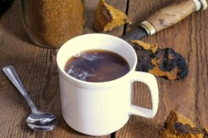 freshly brewed chaga tea in a white mug on a wooden table