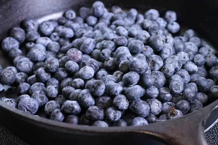 a cast iron pan filled with fresh blueberries