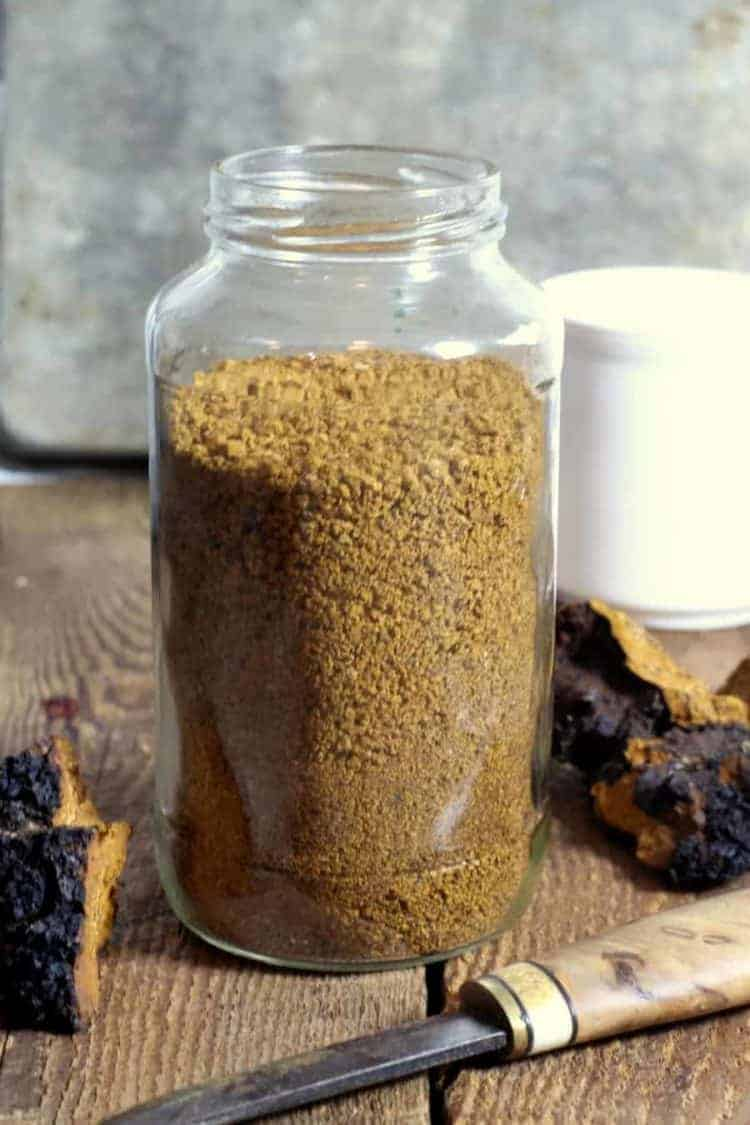 a glass jar filled with coarsely ground chaga mushroom
