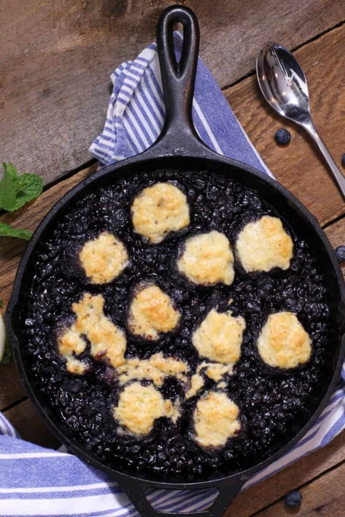 blueberry grunt baked in a cast iron dish with gold brown dumplings in it