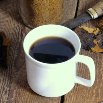 chaga mushroom tea in a white cup on a wooden tabletop