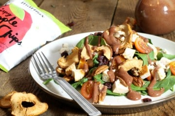 A plate loaded with a chicken spinach salad topped with apple chips, feta, tomato and pecans
