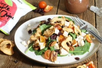 a chicken spinach salad garnished with crispy apple chips, feta, cherry tomatoes and pecans on a wooden table