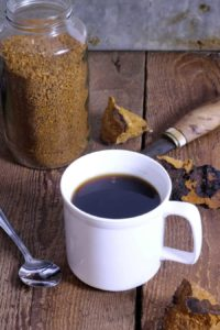 a cup of freshly brewed chaga using ground dried chaga