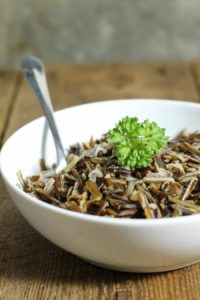 a white bowl filled with cooked wild rice and garnished with parsley