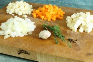 diced onion, carrot, parsnip, and celery root on a cutting board