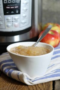 a vertical image of a white bowl of instant pot applesauce