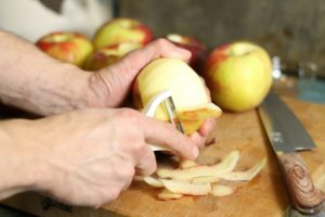 honeycrisp apples being peeled with a white hand held peeler
