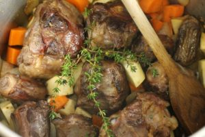 roasted oxtail bones,in a pot with diced vegetables and herbs