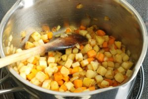 diced root vegetables sauteeing in a pot with butter