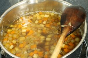 oxtail soup simmering in a pot with vegetable and herb garnishes
