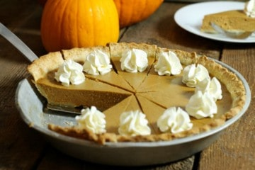 A sliced and garnished homemade pumpkin pie made from scratch, sitting on a wodden table . one pice of pie has been removed.