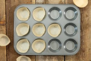a grey muffin tin being lined with parchment paper muffin liners