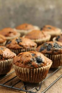 vertical image close close up of a blueberry bran muffin on a black cooling rack