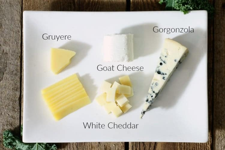 a selection of cheeses on a white plate with labels to identify each