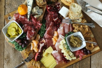A rustic, holiday themed charcuterie platter on a wood board surface