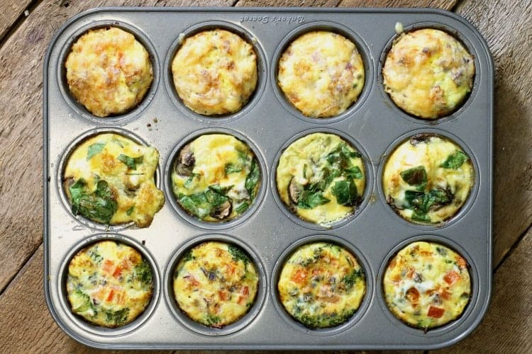 Three different kinds of breakfast egg muffins in a 12 cup muffin tin