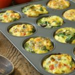 Three different kinds of breakfast egg muffins in a twelve cup muffin tin