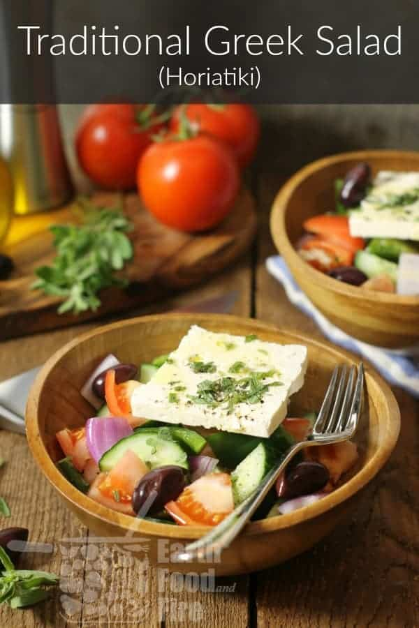 A bowl of traditional Greek salad also known as horiatiki on a wooden table surrounded by various ingredients