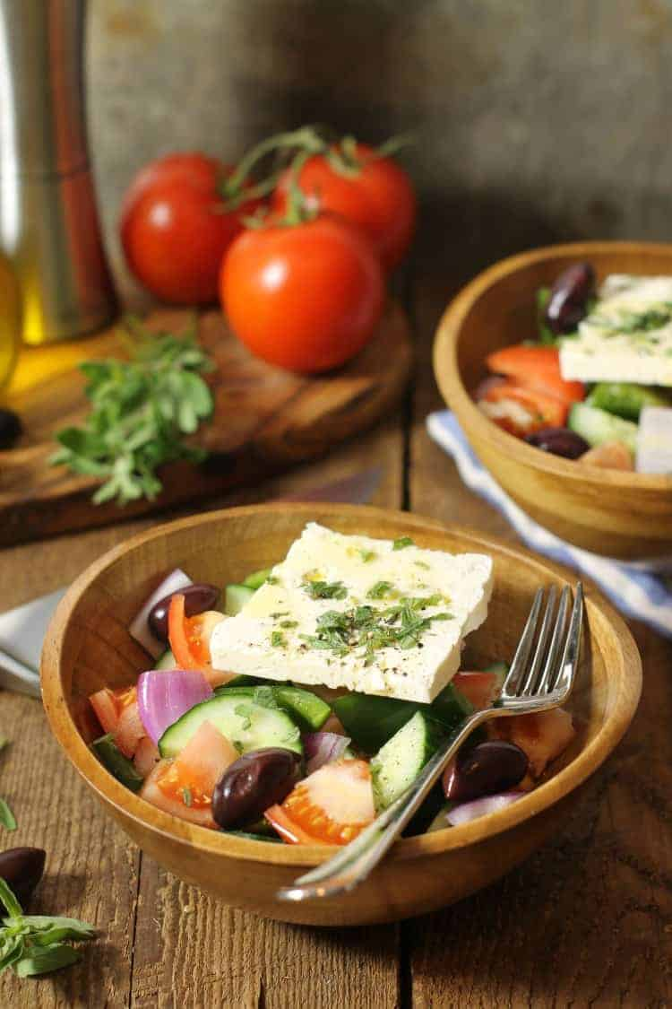 traditional greek salad (horiatiki) served in a wooden bowl with a thick slice of feta on top