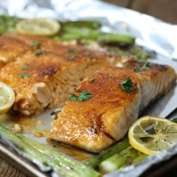 Brown sugar glazed salmon on a tinfoil lined pan surrounded by asparagus