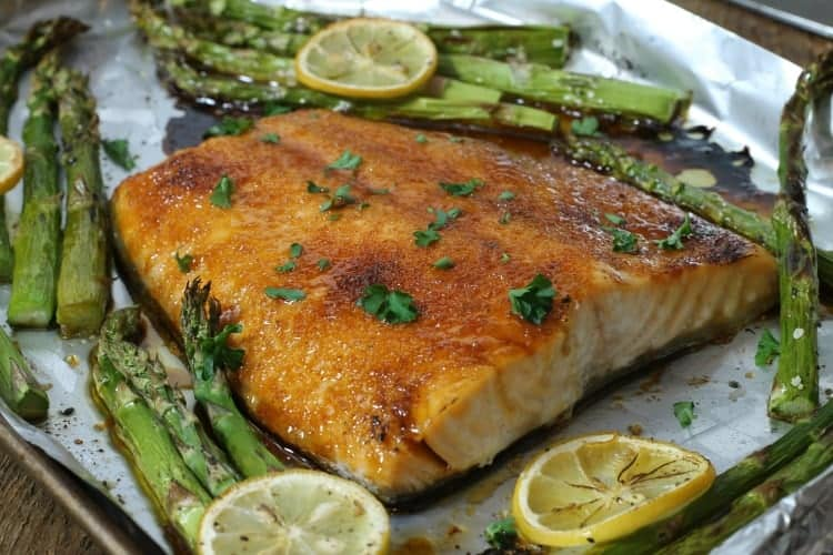 brown sugar glazed baked salmon on a sheetpan after cooking surrounded by asparagus and lemon slices