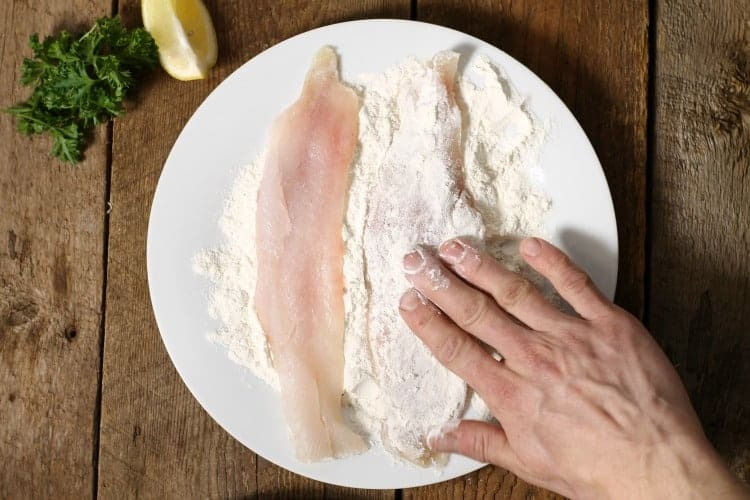 coating haddock with a flour and spice mixture prior to pan frying