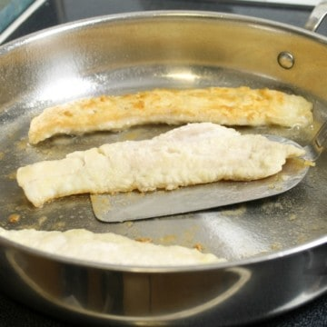 three pan fried pieces of haddock in a white plate with lemon wedges and parsley