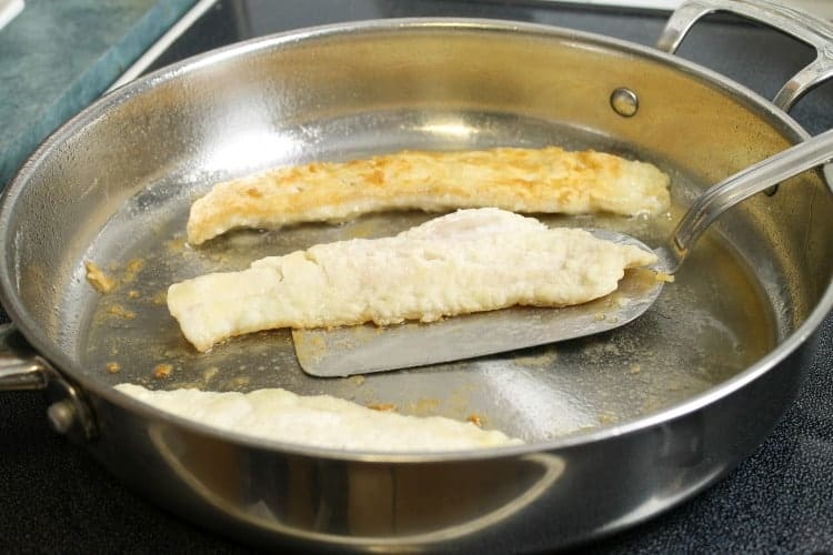 flipping pan fried haddock with a metal spatula