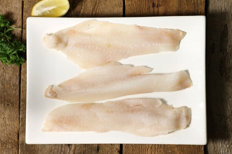 three pieces of fresh haddock on a white plate