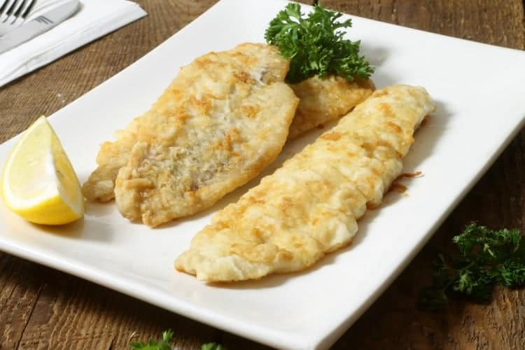 pathree pan fried pieces of haddock in a white plate with lemon wedges and parsley