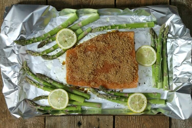 lemon slices and asparagus surrounding a raw pice of salmon on a sheet pan