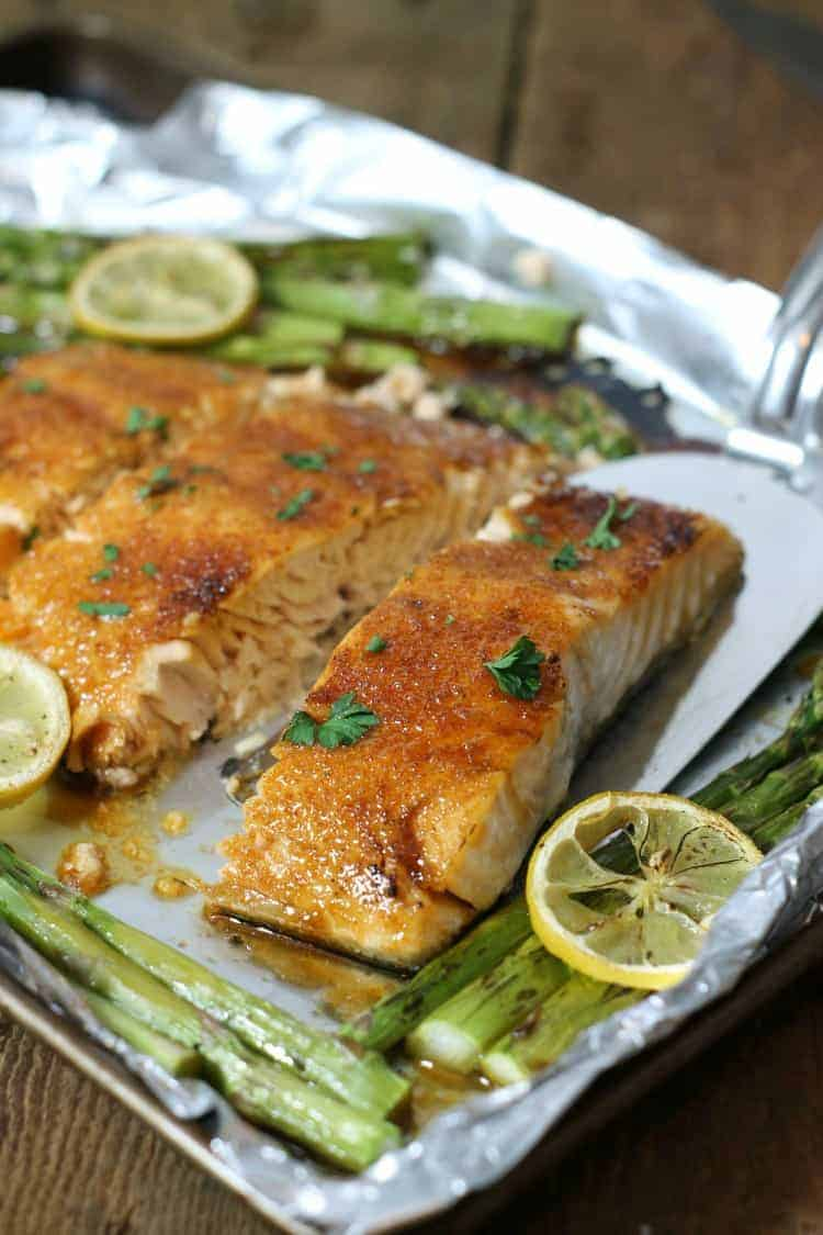 Baked salmon glazed with brown sugar and cut into portions on a tinfoil lined sheetpan