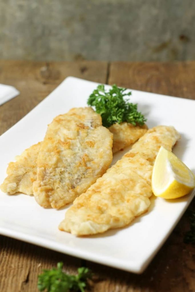 crispy pan fried haddock garnished with parsley and lemon, ready to eat