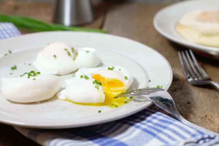 cut open poached eggs on a breakfast plate