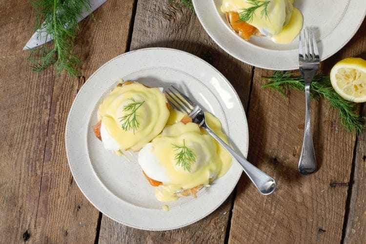 top down view of eggs benedict with smoked salmon on white plates