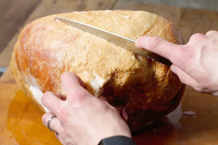 the fat on a ham butt being scored with a knife
