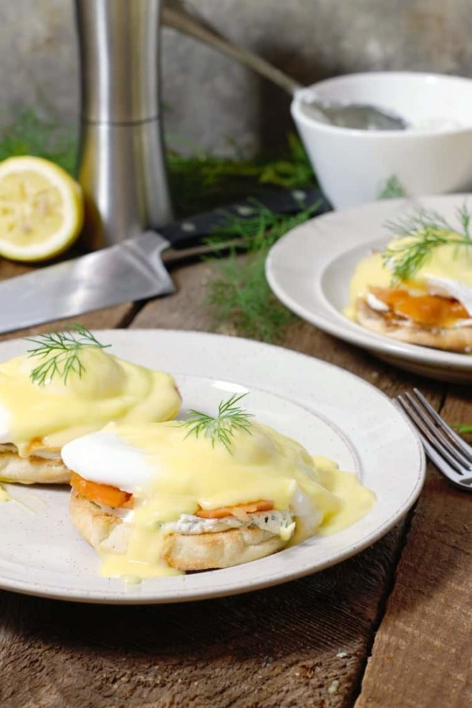 amoked salmon (eggs royale) served on white plates in a rustic table setting