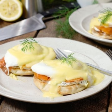 smoked salmon eggs benedict garnished with dill on a white plate