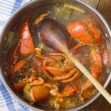 Lobster stock in a large pot with lobster shells, veg and a wooden spoon