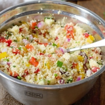 close up shot of Mediterranean Couscous Salad in a wooden bowl