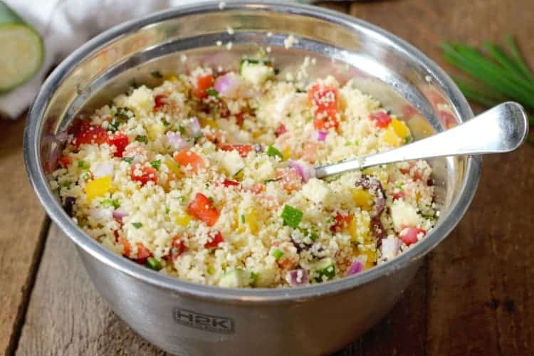 A metal bowl of Mediterranean Couscous Salad ready to be eaten or stored as meal prep