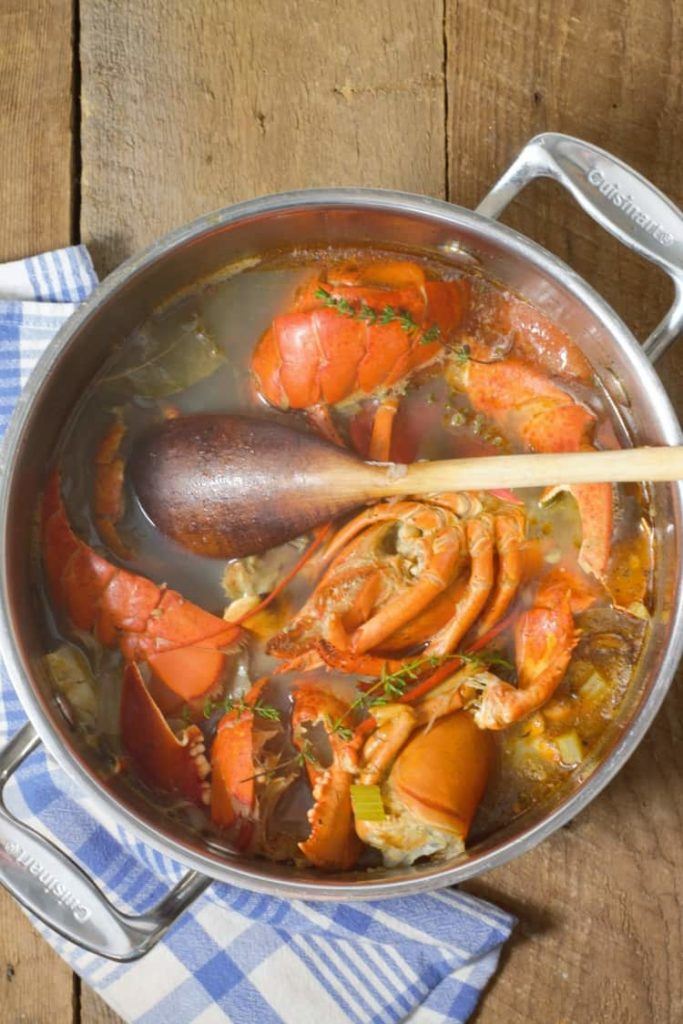 vertical image of lobster stock in a large pot after cooking
