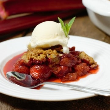 a portion of strawberry rhubarb crumble topped with vanilla icecream