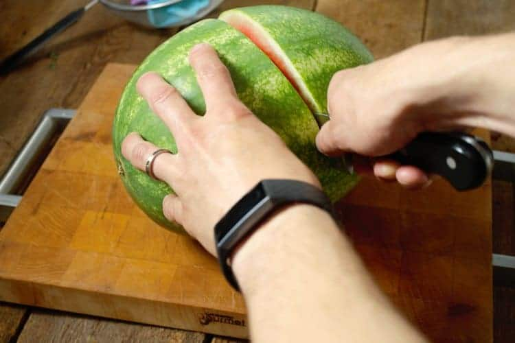 a watermelon being cut in half on a wooden cutting board