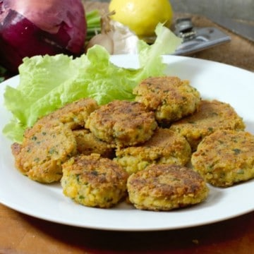 homemade falafel patties on a white plate surrounded by garnishes