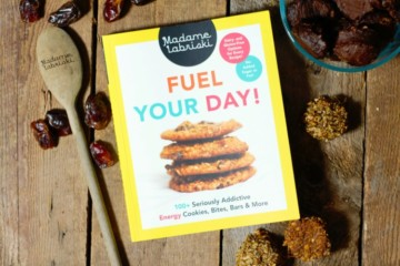 a copy of the cookbook 'Fuel Your Day!' by madame Labriski on a barn board tabletop surrounded by baked treats