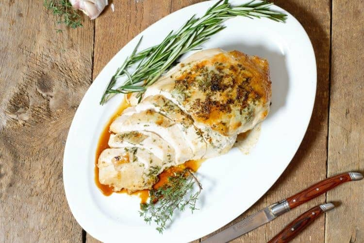 garlic and herb roast turkey breast sliced and served on a white platter