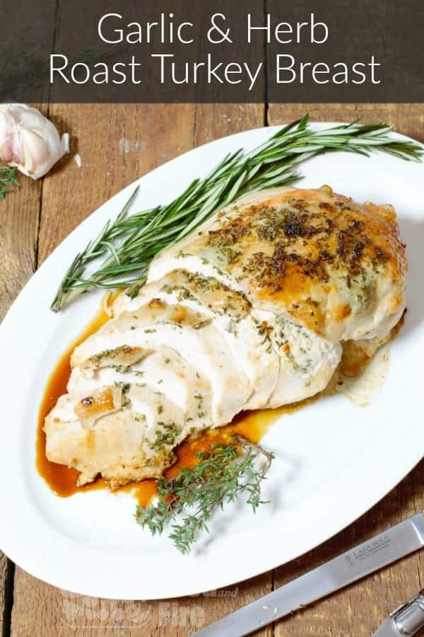 garlic and herb roasted turkey breast on a white serving platter
