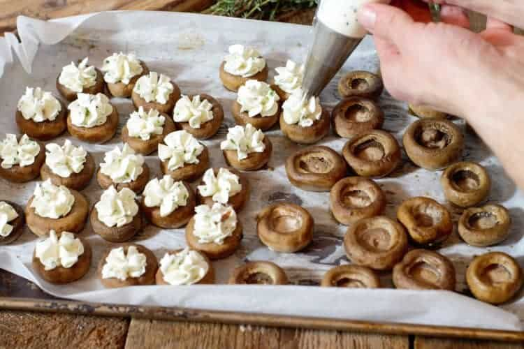 piping roast garlic flavored goat cheese into roasted mushroom caps